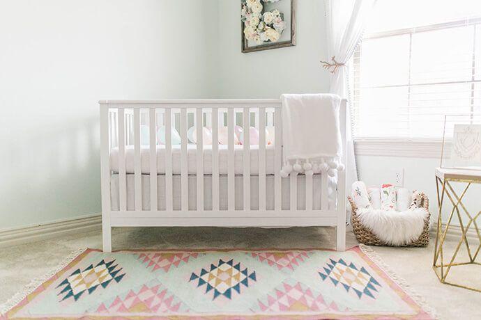 Vivero neutro de menta con enfoque simple y alfombra tipo colcha en el piso
