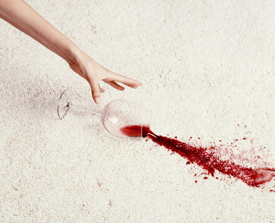 wine spilling on a white carpet