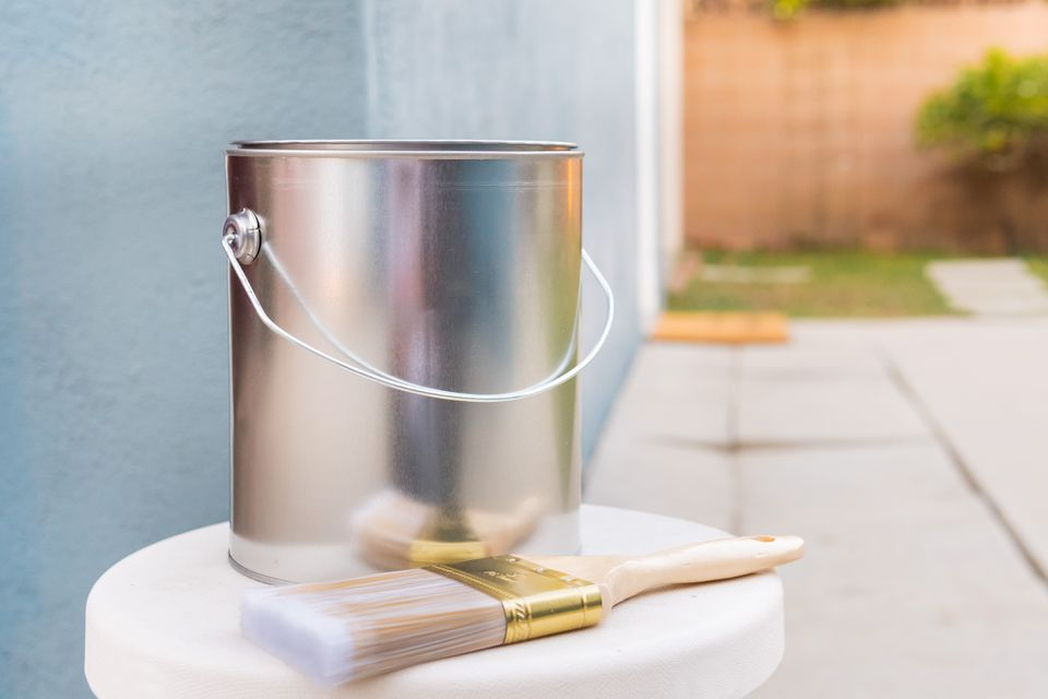 Metal paint bucket on white surface with paint brush in front of blue exterior wall