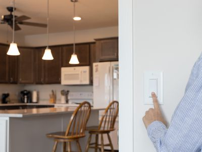 Light switch being pressed to turn off kitchen lights and lower electricity bill