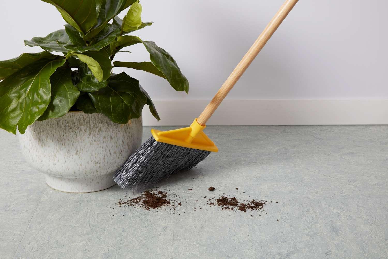 Sweeping dirt on linoleum floor