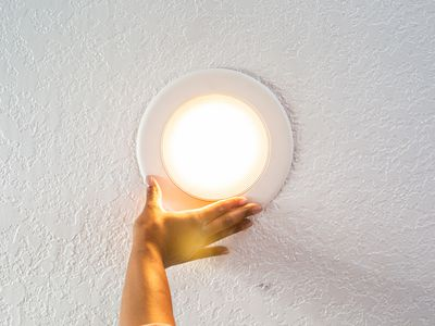 Recessed lighting held up by hand with light on
