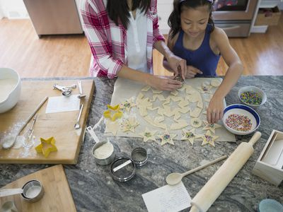 Two people cooking on a natural granite slab countertop