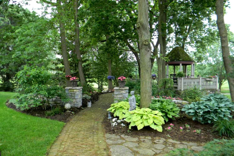 árboles y jardines que bordean un camino de piedra