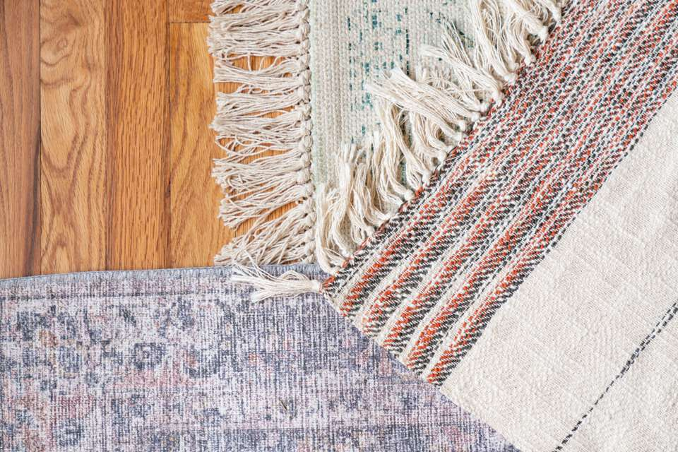 Hand-knotted and hand tufted rugs compared on wooden floor