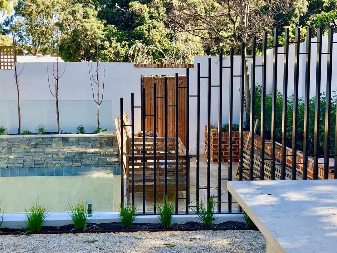 A small backyard with a matte black intricate fence and glass wall fence around a pool.
