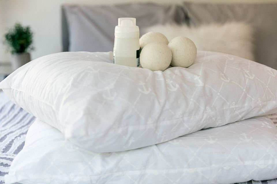 Pillows on a bed with detergent and dryer balls