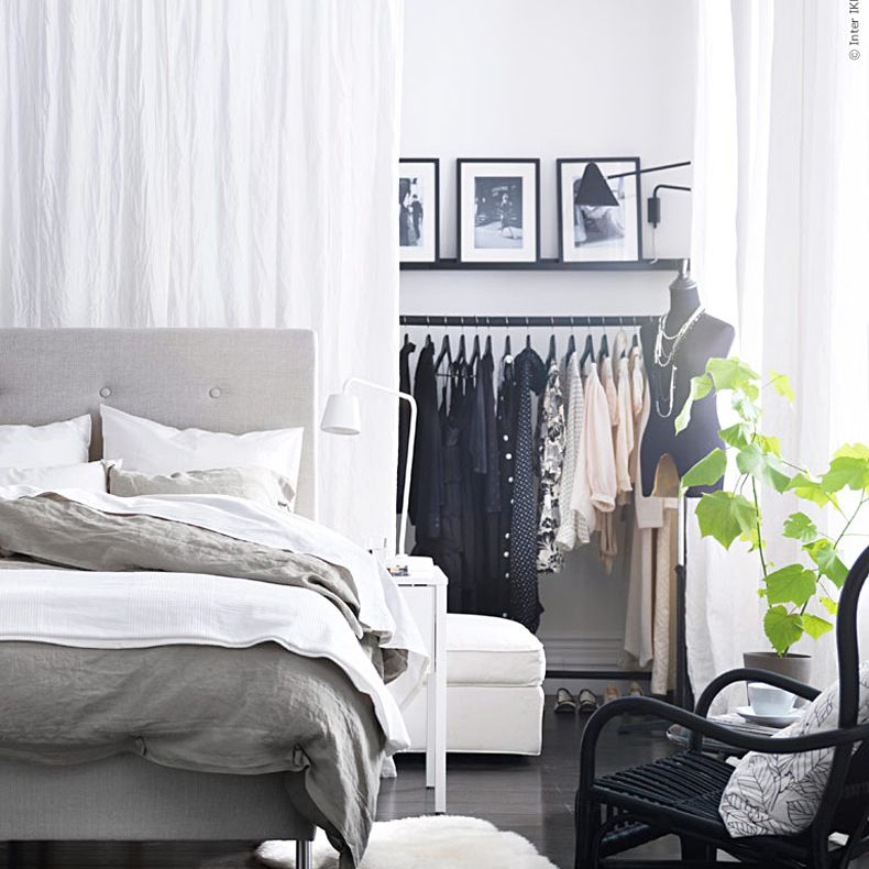 Space behind a bed set off with a white curtain