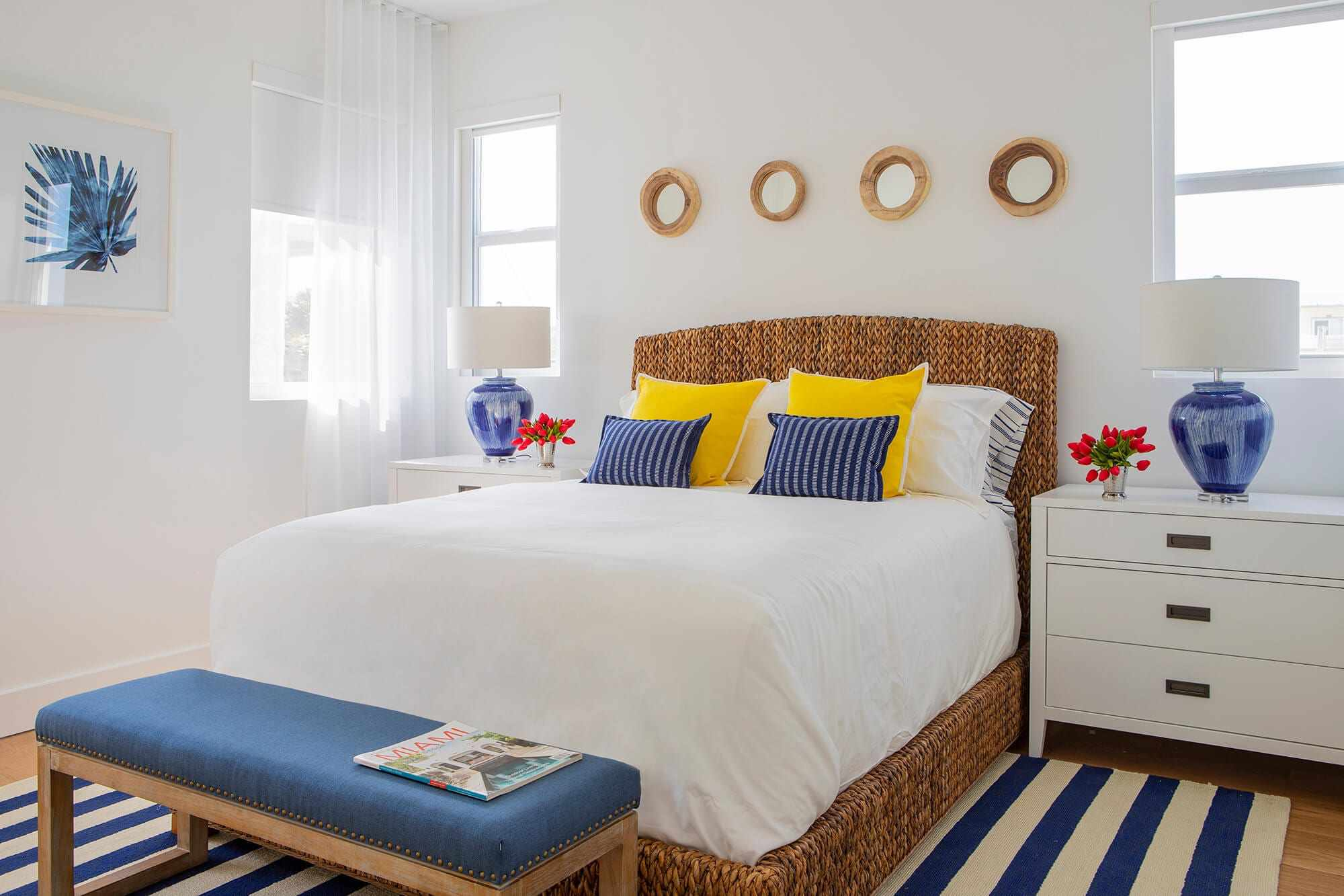 primary bedroom with white walls and bed, with pops of yellows, blue, and red