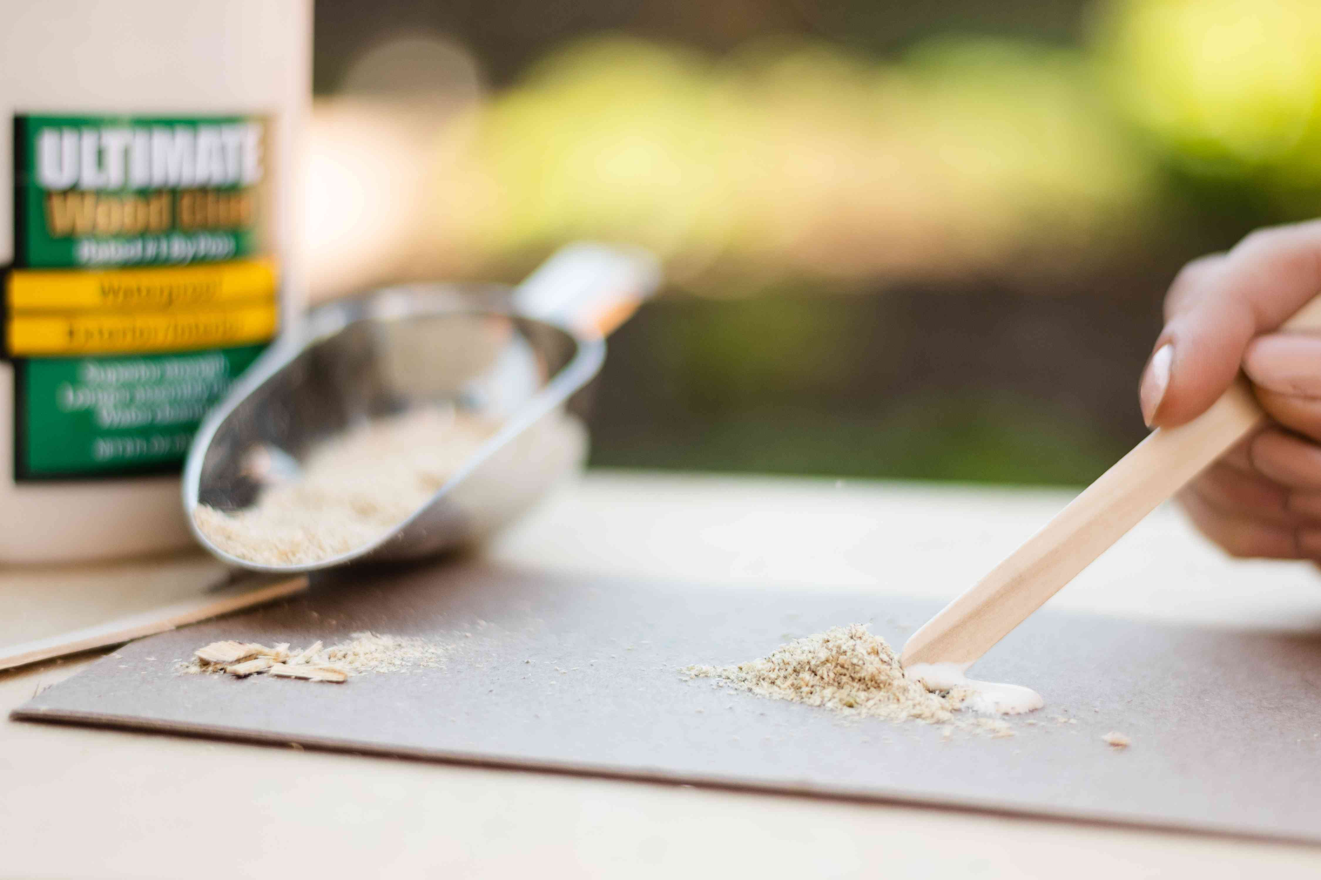 Sawdust and wood glue mixed with stick next to scoop of sawdust