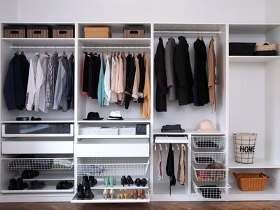a closet with clothes on hangers and shoes in storage shelves