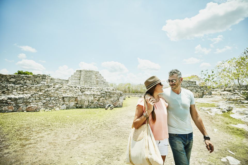 Wife and husband with arms around each other exploring Mayapan ruins during vacation