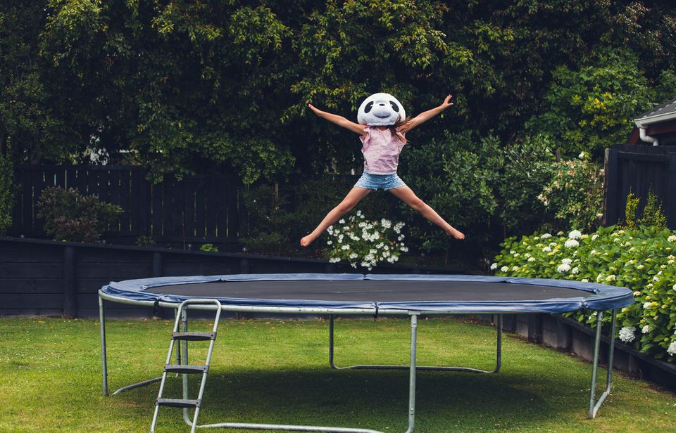 girl with panda mask bouncing on trampoline