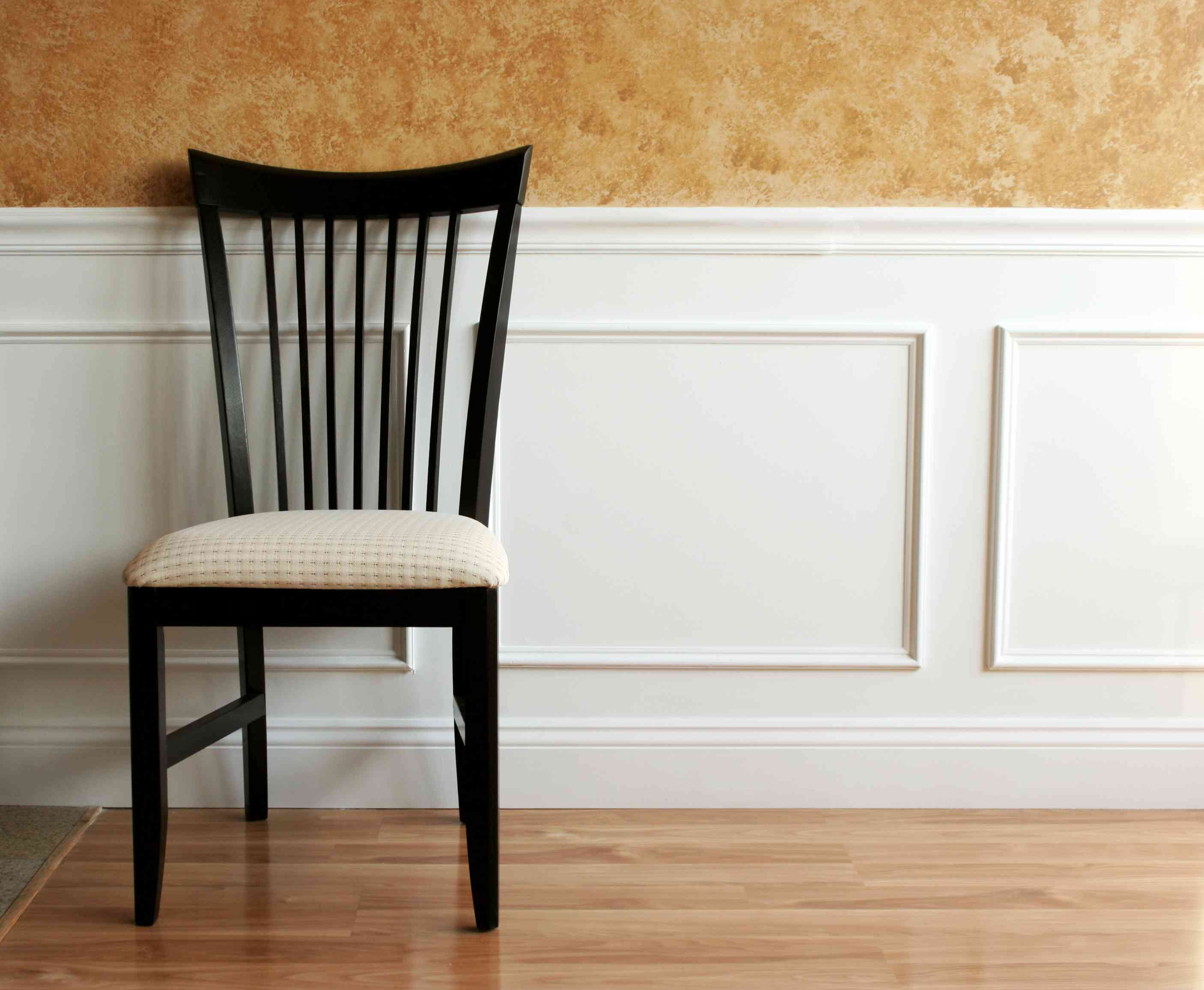 White wainscot panel with dining chair against it