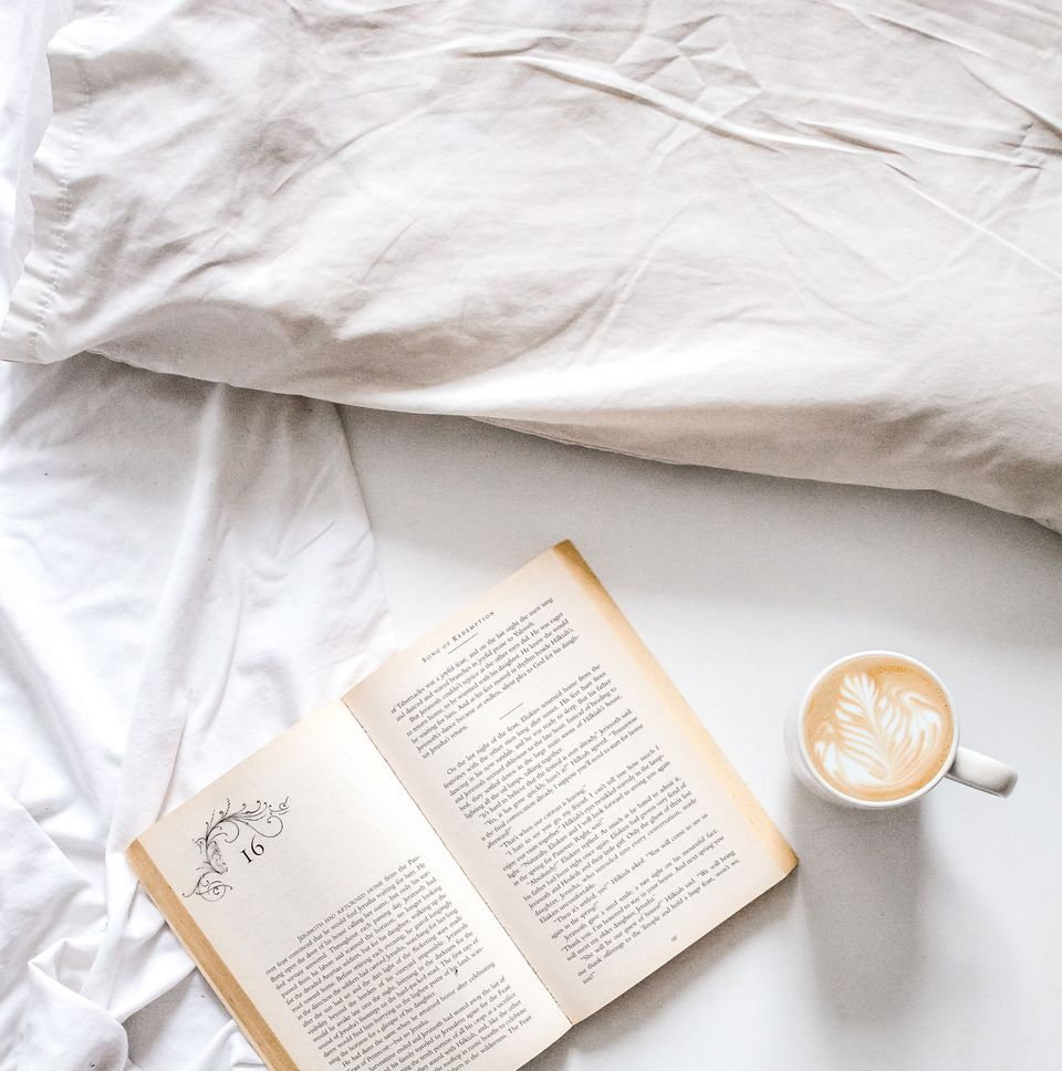 Linen bedding with book and coffee mug