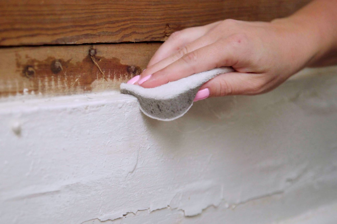 White baseboards being cleaned by hand with wet sponge