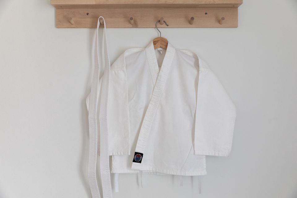 Karate uniform shirt and belt handing on wooden shelf