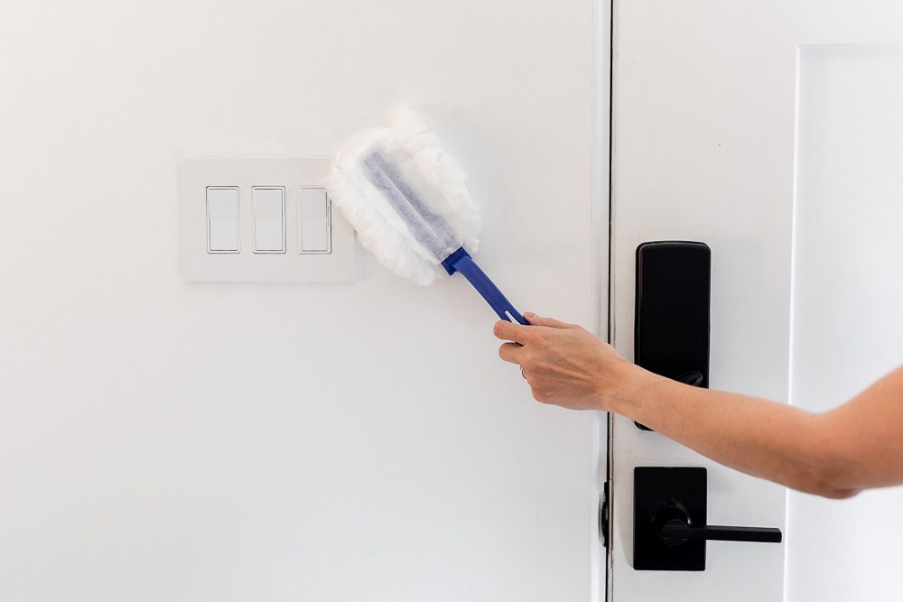Dust being removed from wall with white and blue duster