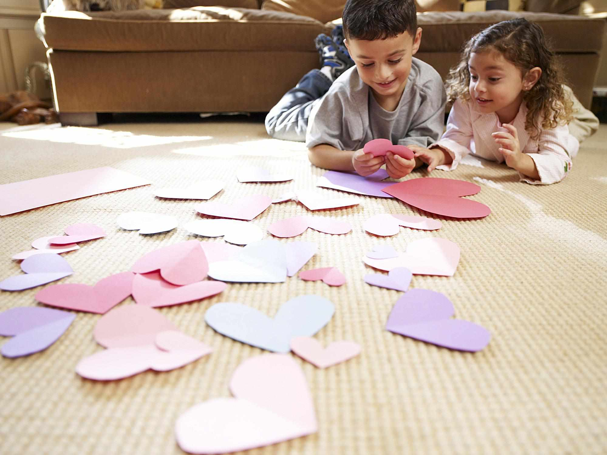 A boy and girl playing with paper hearts.