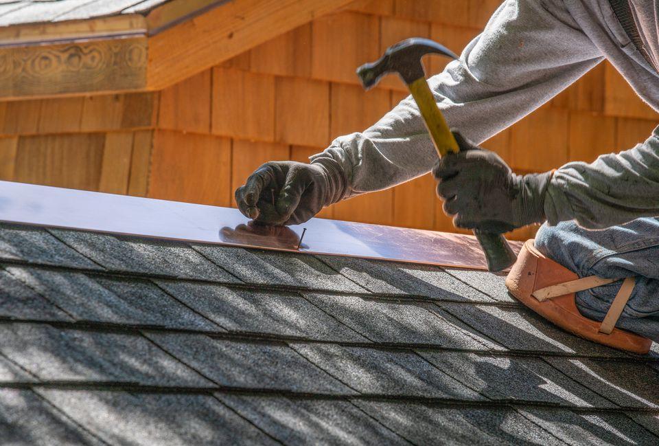 Man installing asphalt roof
