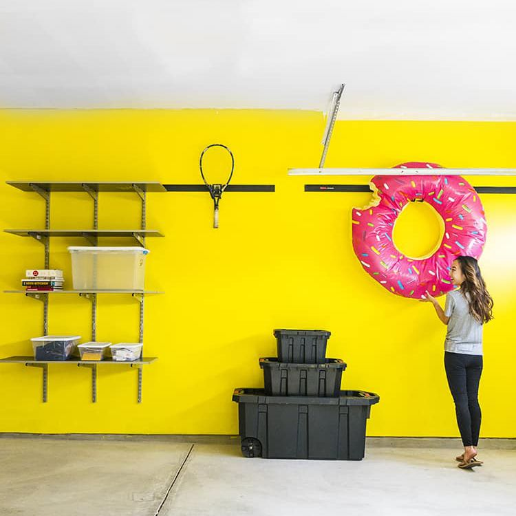 A girl hanging up an inflatable donut in a yellow garage.