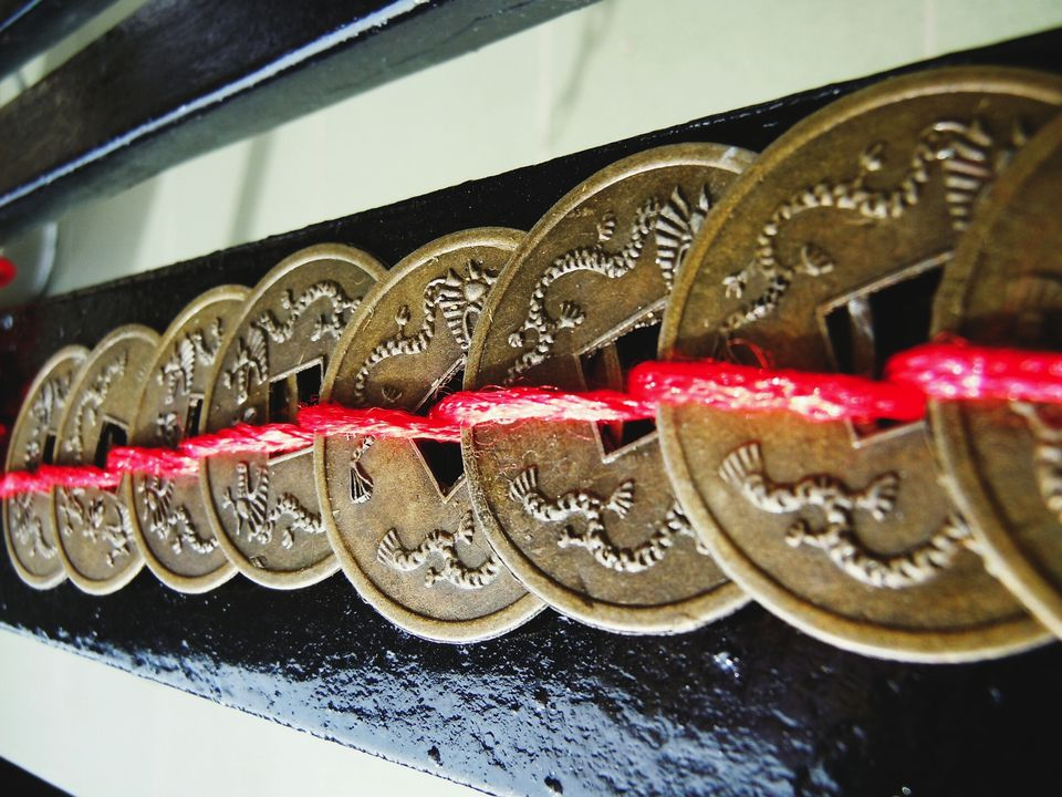 Close-Up Of Antique Feng Shui Coins Tied Up By Red Thread.