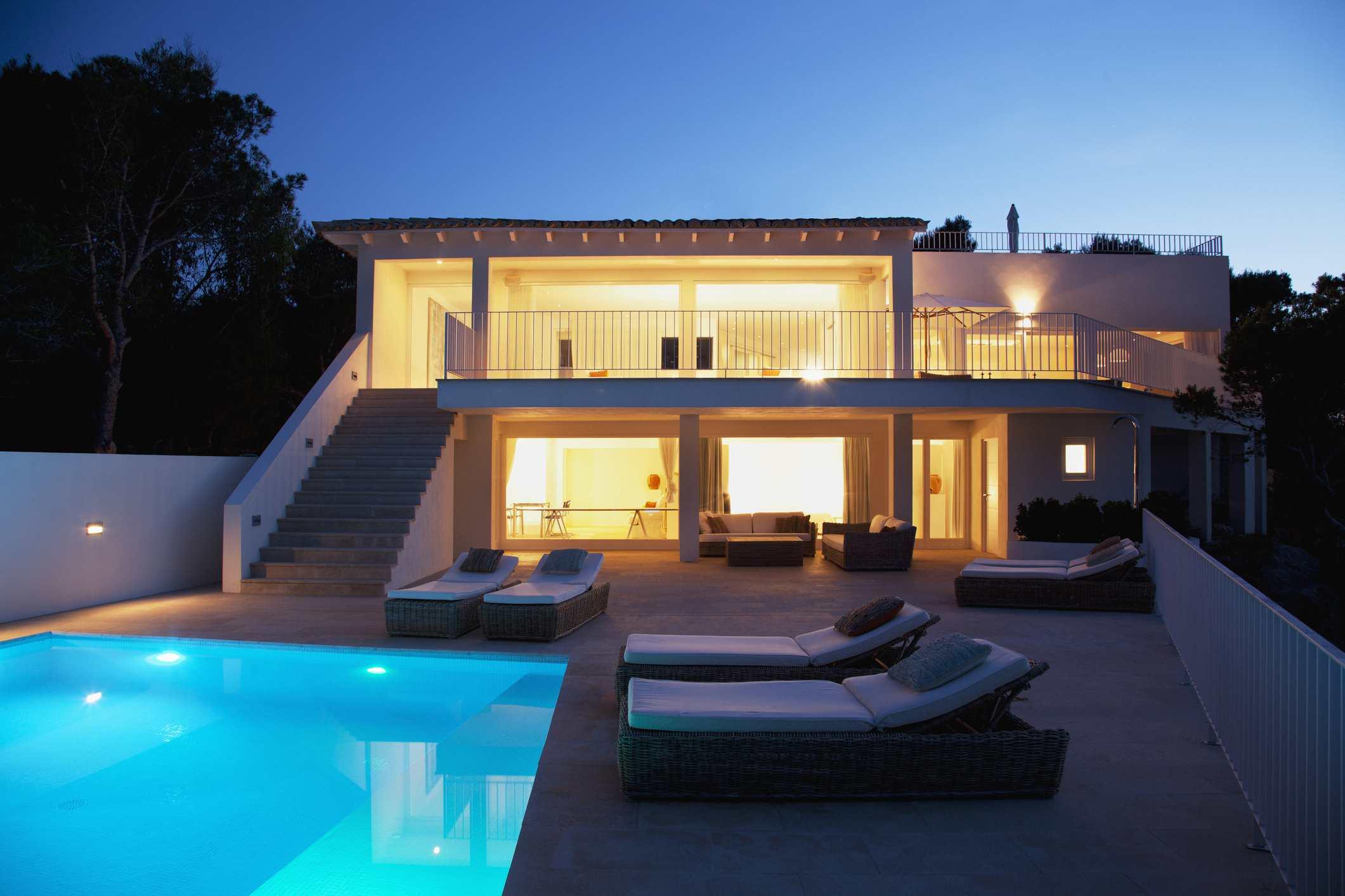 Una sal piscina de agua por la noche con una casa iluminada cerca