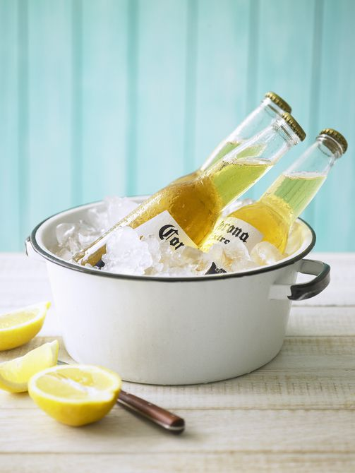 Tres botellas de cerveza Corona en una olla con hielo y limones sobre la mesa