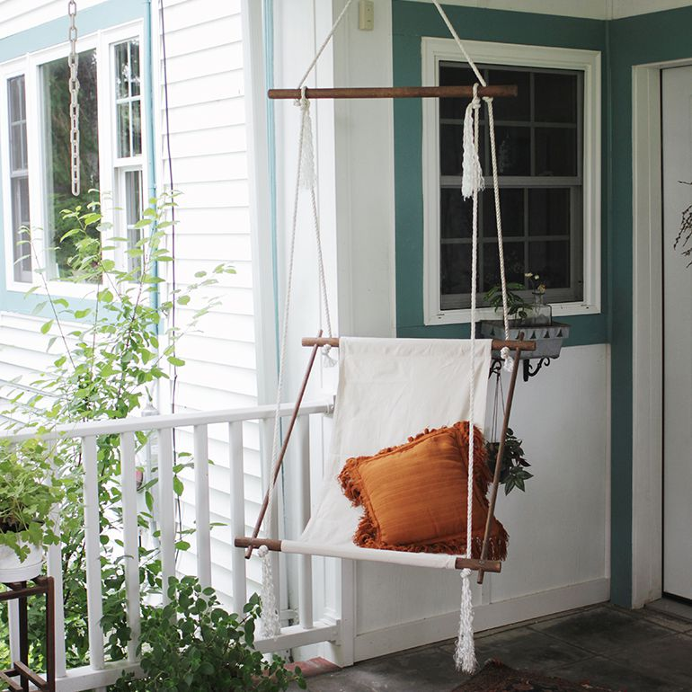 A hanging hammock chair on a porch