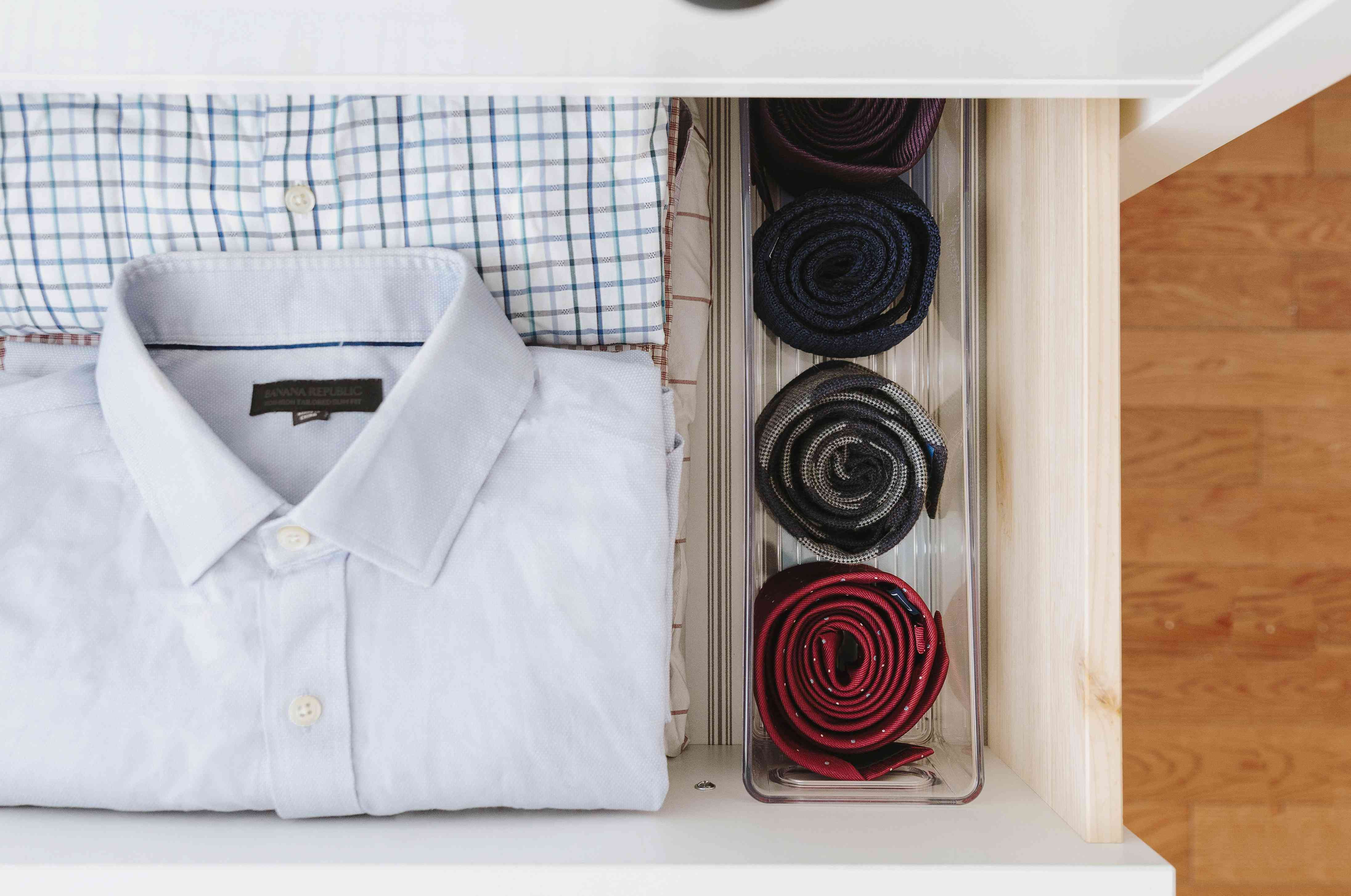 ties rolled up and stored in a plastic organizer