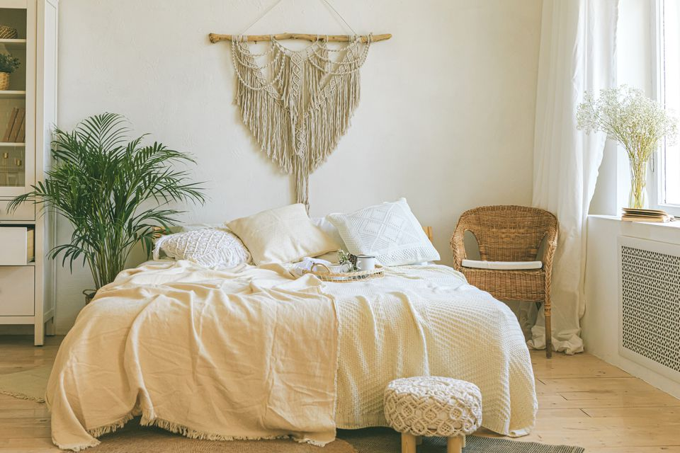 A bed in the center of a boho bedroom