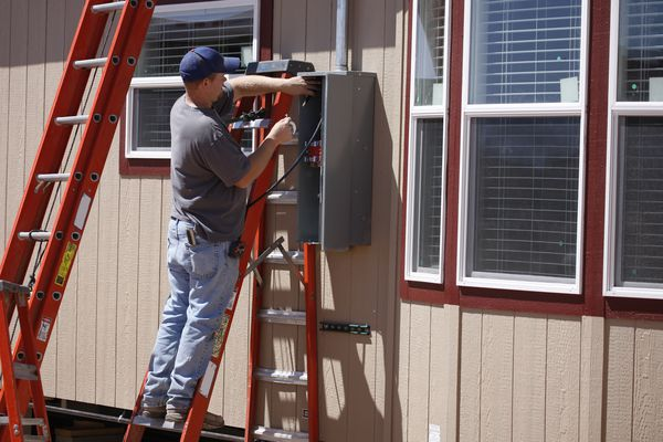 Electrician Working on Electrical Service Panel