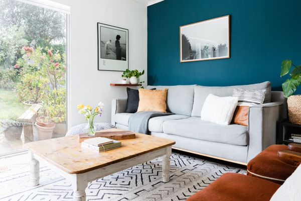 Deep blue accent wall in living room with gray couch next to floor to ceiling window