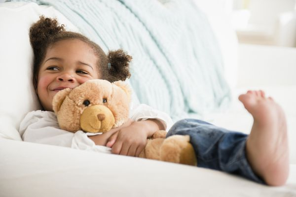 Black girl hugging teddy bear and smiling