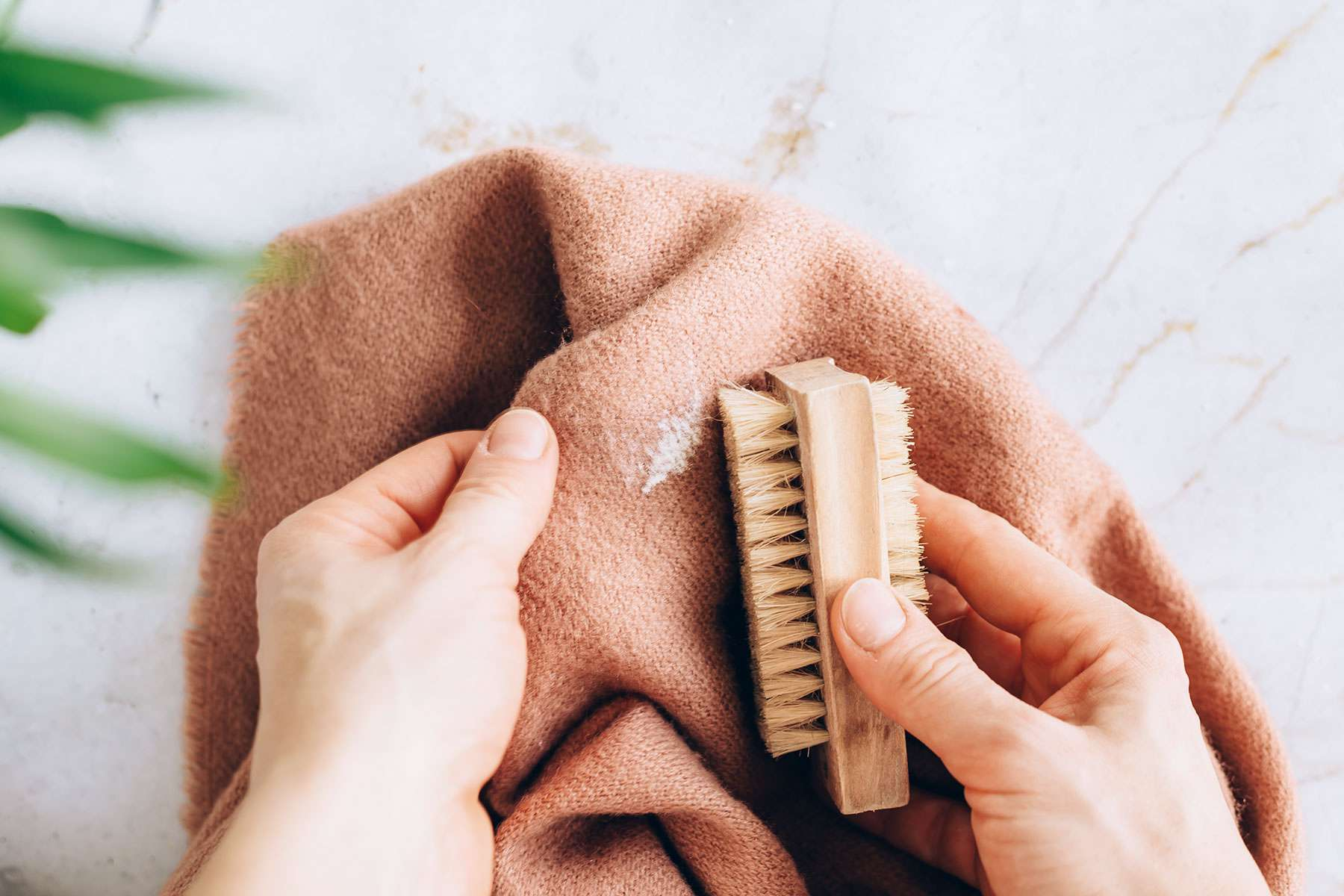 using a soft-bristled brush to remove salt stains