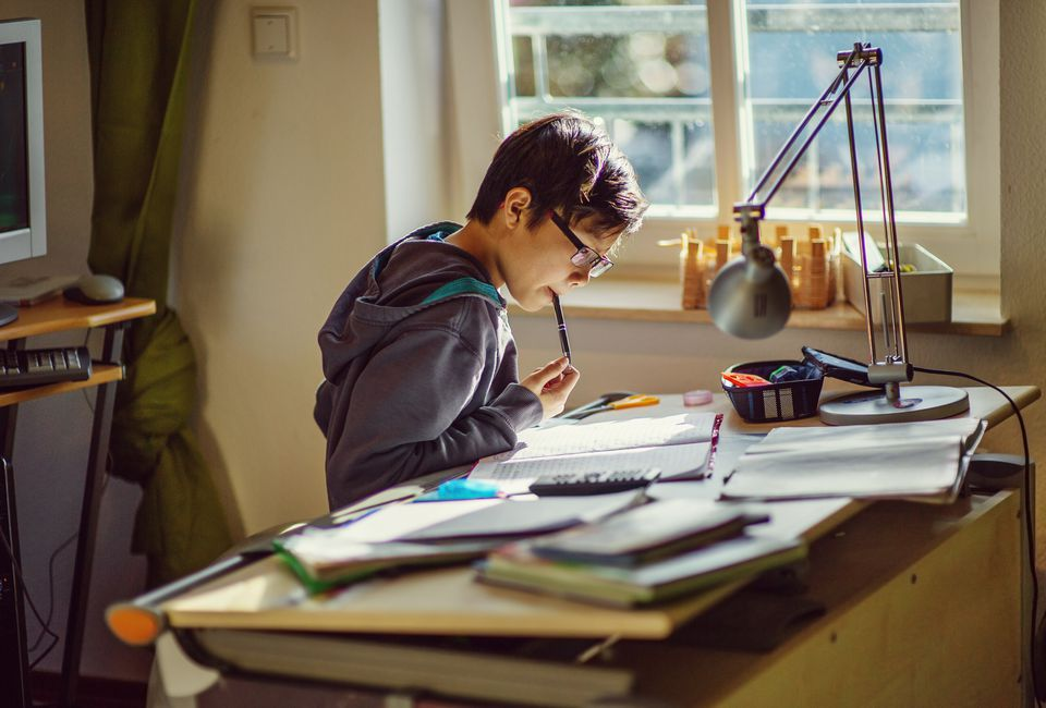 Boy doing his homework at a desk in his room