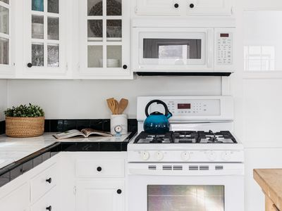 Modern kitchen with all white cabinets and appliances with light decor on black and white sqaure tiles