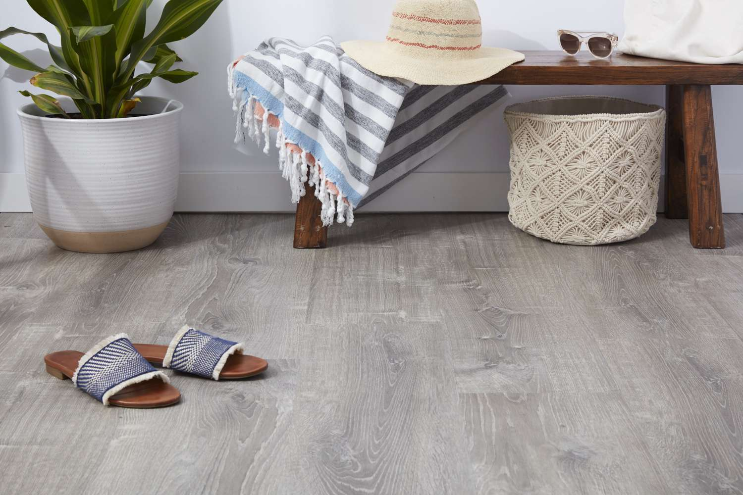 Luxury vinyl plank flooring with sandals and wooden bench with beach items next to houseplant