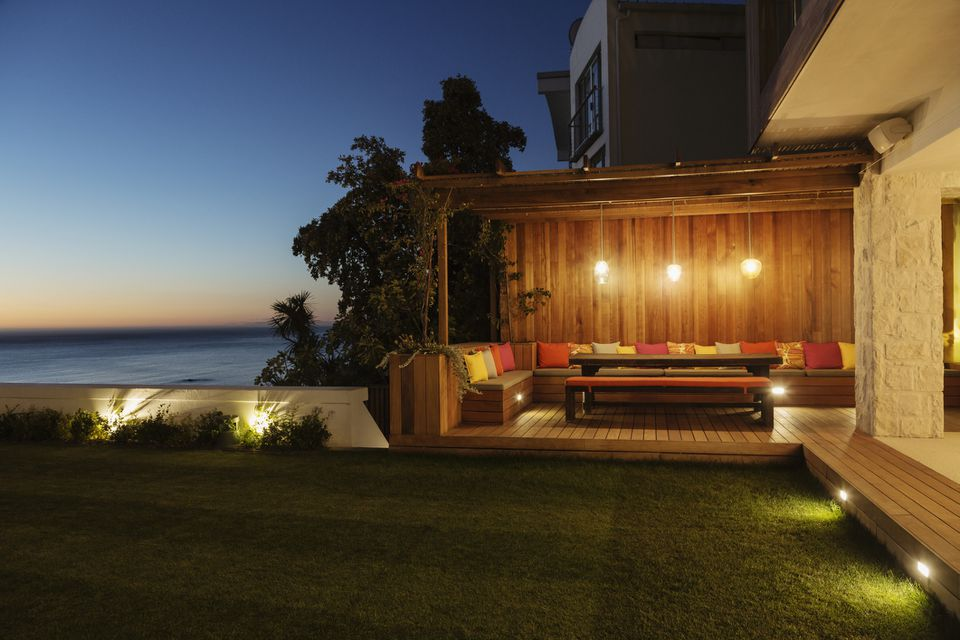 A lush backyard lawn and illuminated patio at dusk