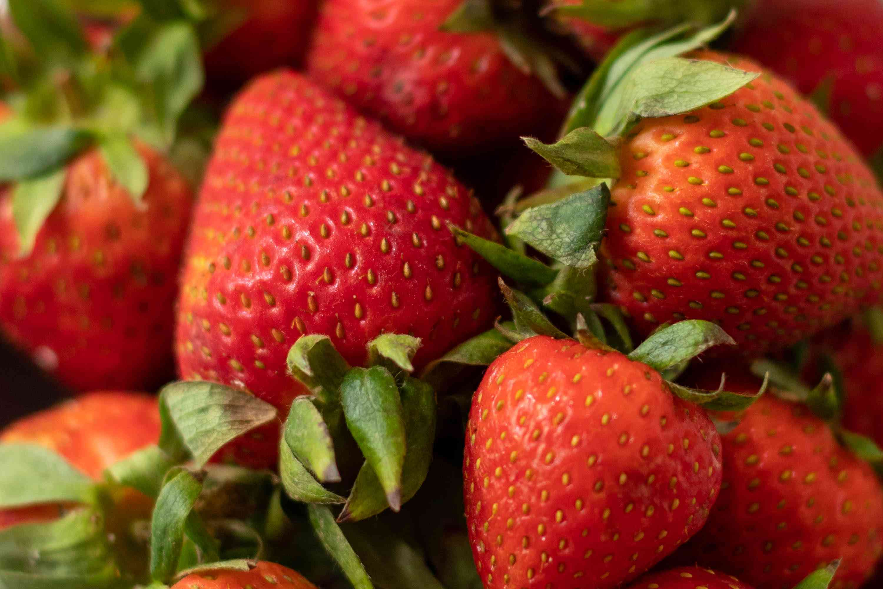 Bright yellow-green seeds covering red strawberry fruit