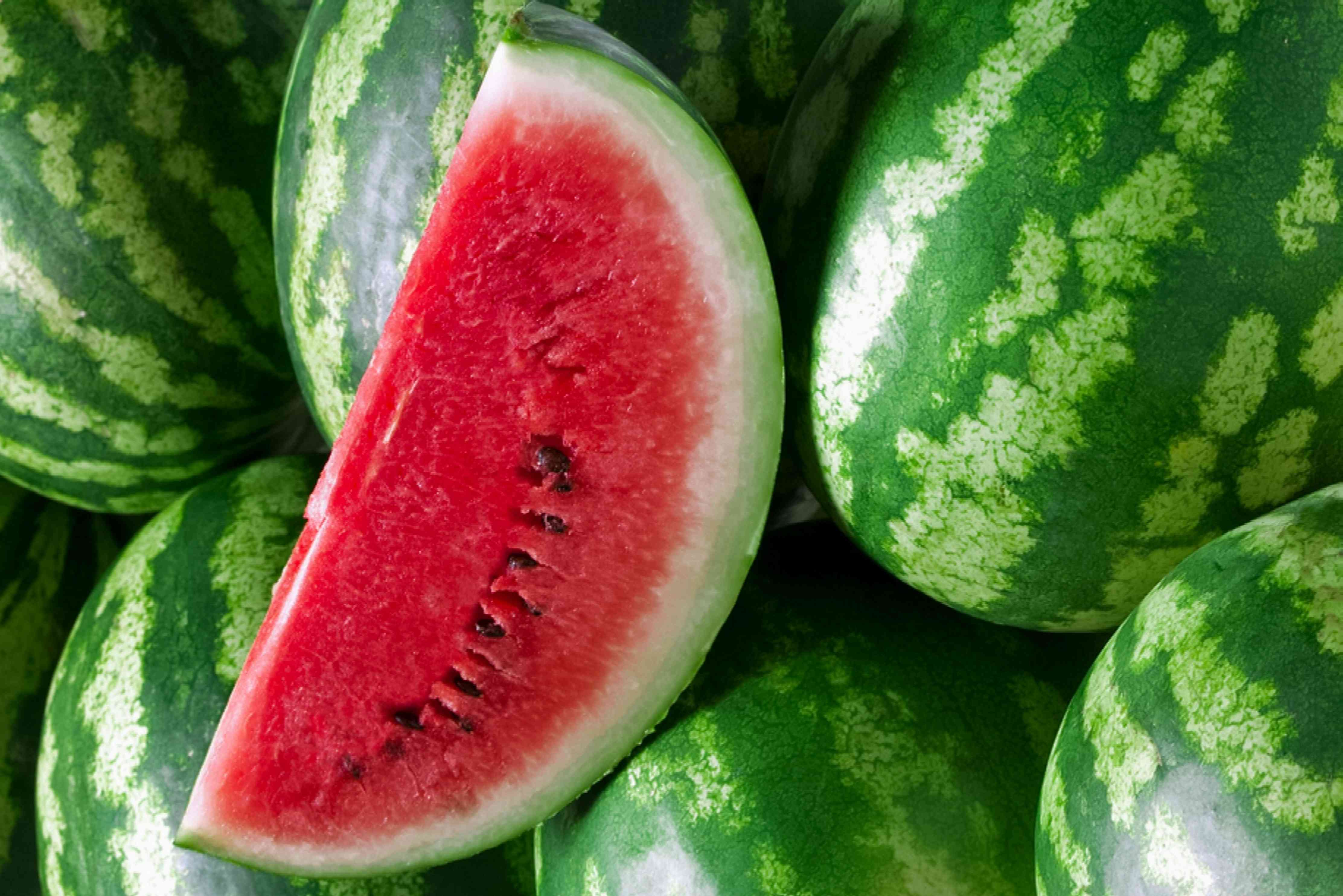 Cut slice of watermelon on a pile of whole watermelons