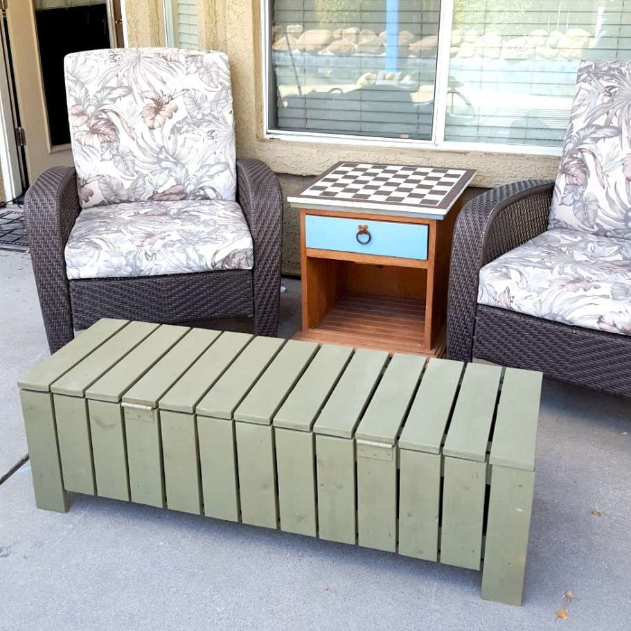 A green storage bench on a pork with chairs