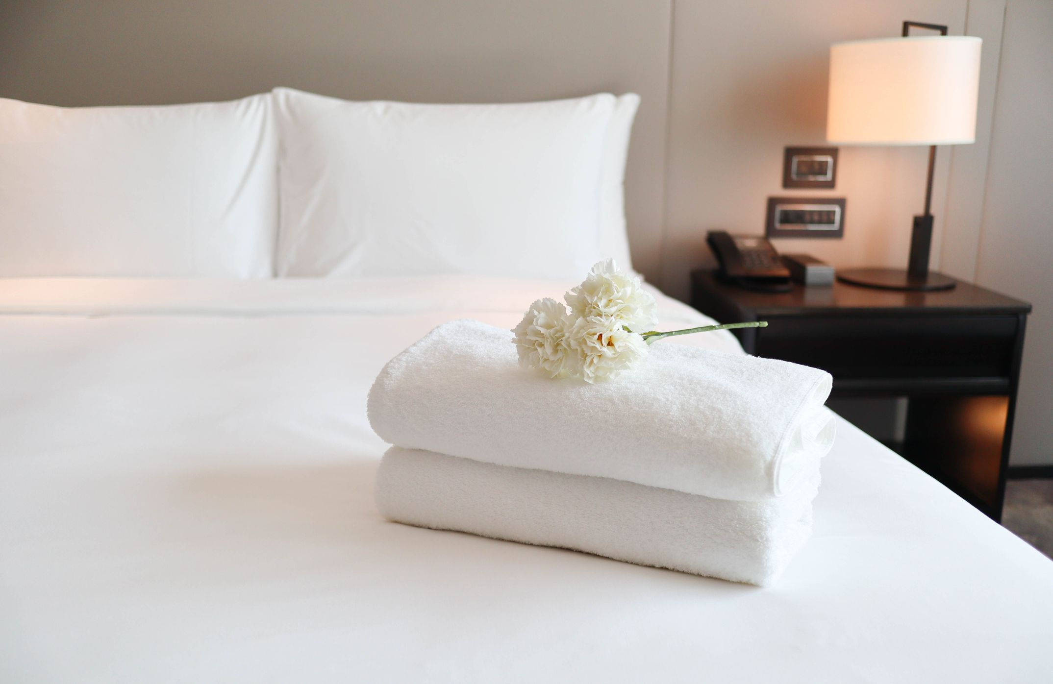Plush white towels on a freshly made bed