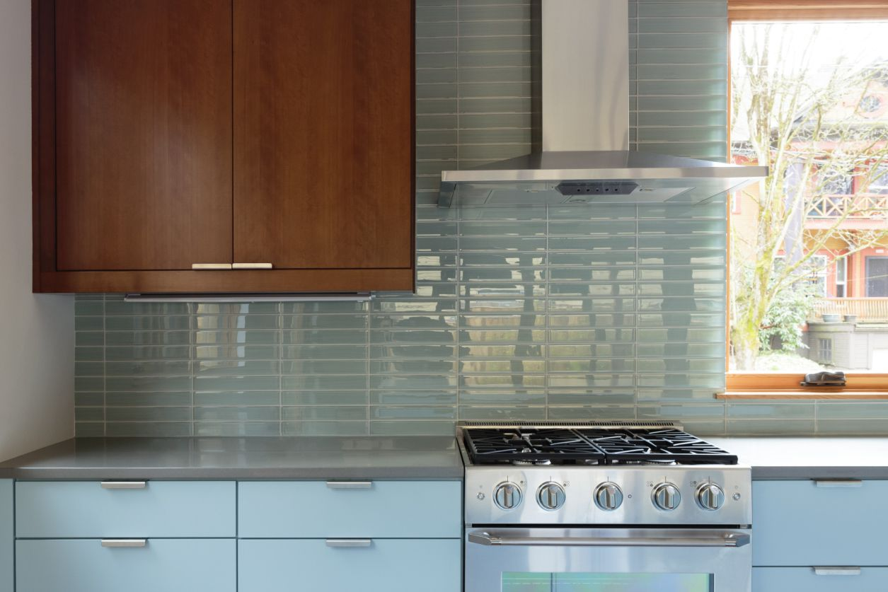 Kitchen with blue backsplash and wooden cabinets