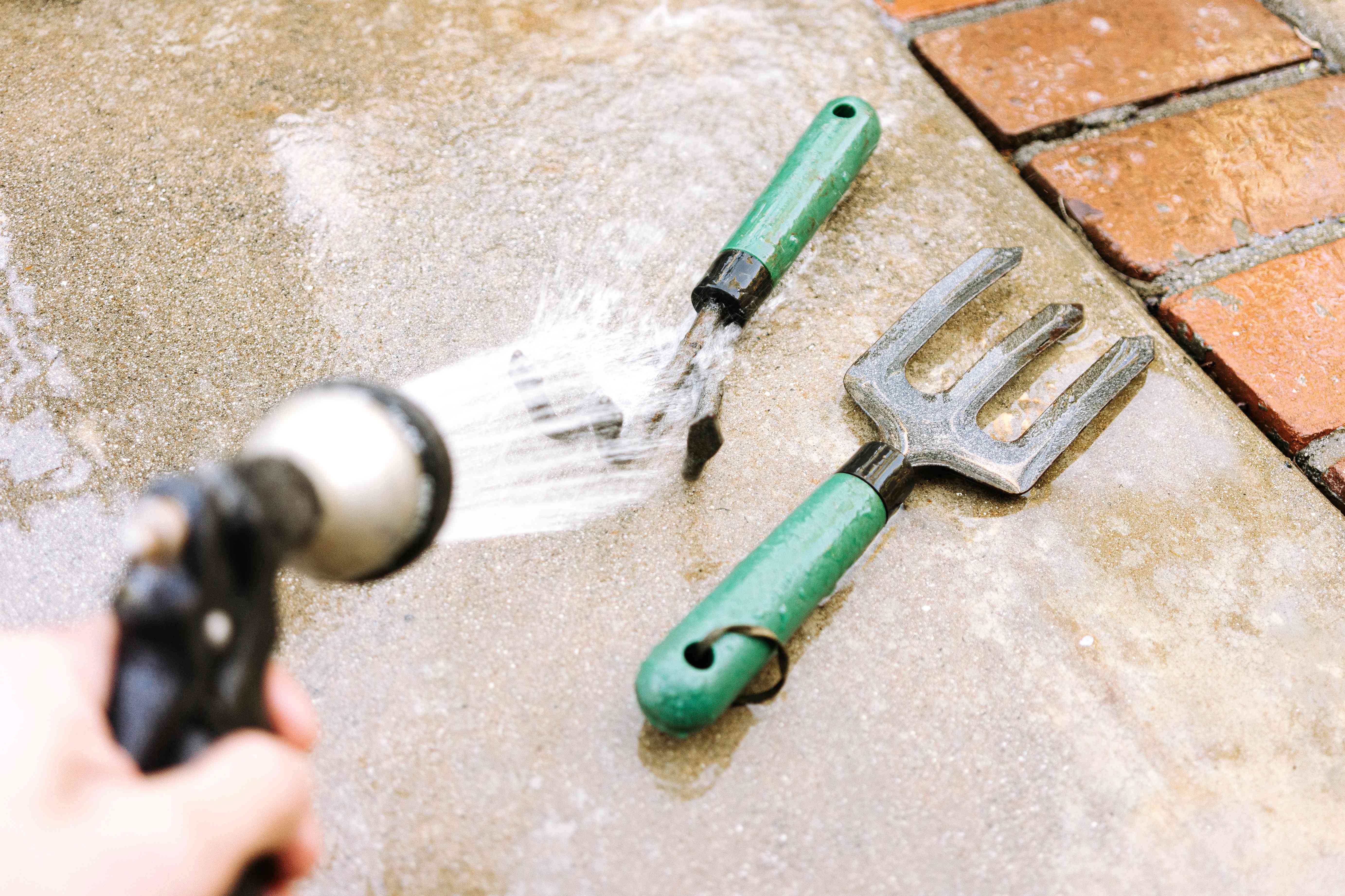 rinsing off tools with a garden hose