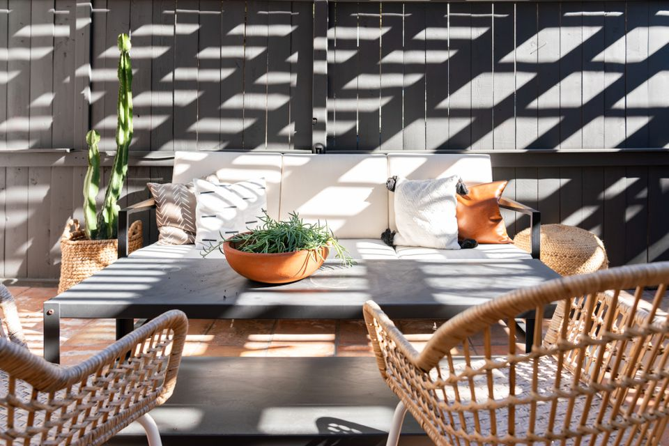 Tiny backyard with decorated seating, gray table and wicker chairs