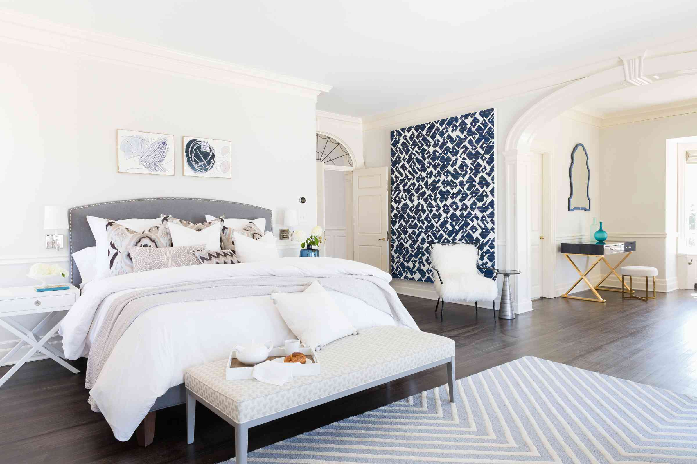 Beautiful white bedroom with a navy and white accent wall