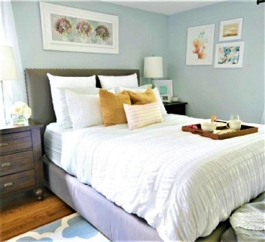 Dormitorio principal con edredón blanco y cuadros en la pared