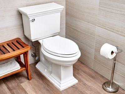 White toilet next to wooden bench with folded towel and toilet paper stand