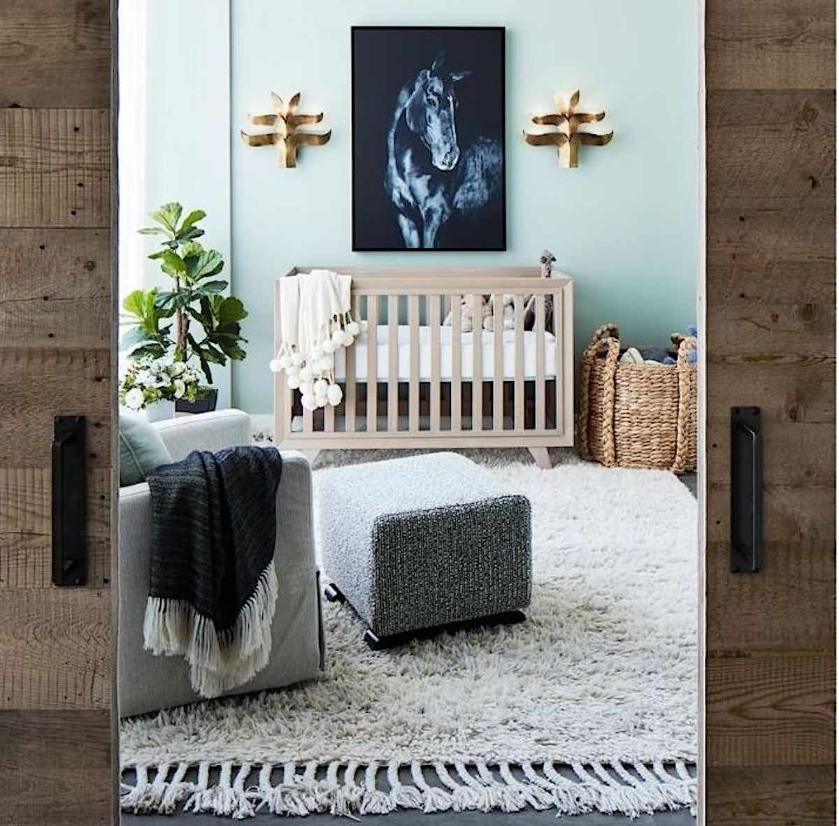blue nursery with tan crib and artwork of blue horse hanging above
